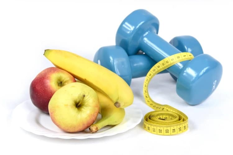 Dumbells Tape and a Plate of Fruits