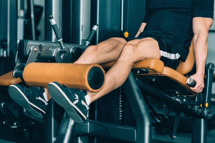 Muscular man exercising in gym, leg extension machine workout