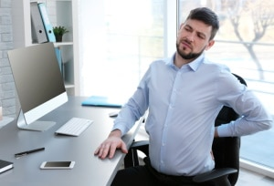 Man Holding Back in Pain While Working