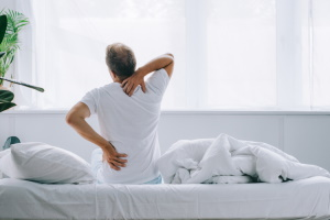 Man Sitting in Pain on Bed Holding Back