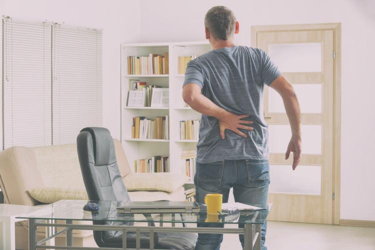 Man Standing Holding Lower Back