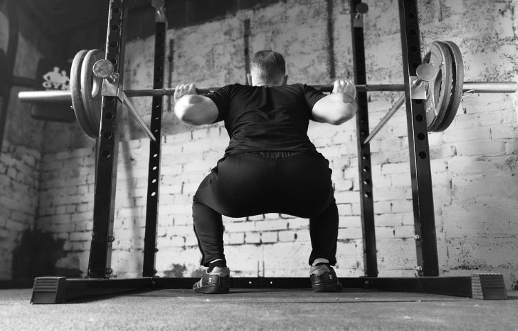 Man in Squatting Position Inside a Power Rack