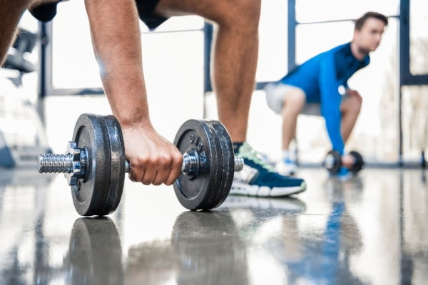 Men Workout With Dumbbells at Gym