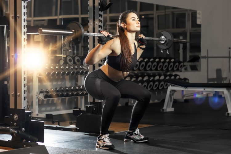 Powerfull attractive woman squatting with a barbell